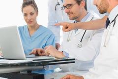 Группа в составе сконцентрированные доктора используя компьтер-книжку совместно Стоковые Изображения