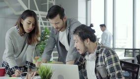 Группа в составе случайно одетые бизнесмены обсуждая идеи в умной случайной носке работая на ноутбуке пока сидящ на столе сток-видео