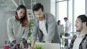 Группа в составе случайно одетые бизнесмены обсуждая идеи в умной случайной носке работая на ноутбуке пока сидящ на столе видеоматериал