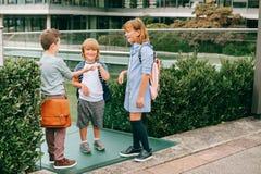 Группа в составе 3 смешных дет нося рюкзаки идя назад к школе Стоковые Фотографии RF