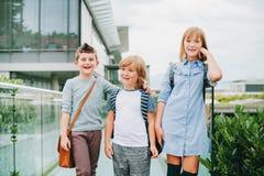 Группа в составе 3 смешных дет нося рюкзаки идя назад к школе Стоковое Изображение
