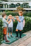Группа в составе 3 смешных дет нося рюкзаки идя назад к школе Стоковая Фотография RF