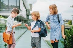 Группа в составе 3 смешных дет нося рюкзаки идя назад к школе Стоковое Изображение RF