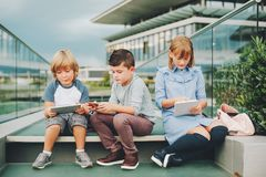Группа в составе 3 смешных дет нося рюкзаки идя назад к школе Стоковые Изображения