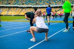 Группа в составе спортсмены делает exersises на стадионе сидение на корточках и простирание стоковые изображения rf