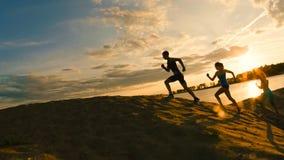 Группа в составе спортсмены - 2 девушки и парень исчезают гора, около реки на сумраке Стоковая Фотография