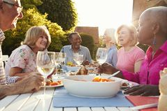 Группа в составе старшие друзья наслаждаясь внешним официальныйом обед дома стоковые фото