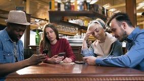 Группа в составе стильные друзья хипстера используя умный телефон во время отдыхать в пабе, бар сток-видео