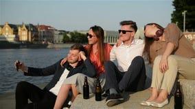 Группа в составе студенты делая Selfie над зданием университета 4 молодых счастливых студента делая Selfie и усмехаться сток-видео