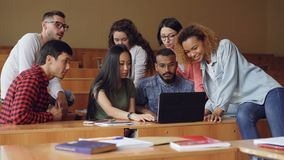 Группа в составе студенты использует компьтер-книжку сидя в классе и говорящ, молодые люди работает на проекте самомоднейше видеоматериал