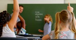 Группа в составе студенты сидя на столе и поднимая руки в классе в школе 4k акции видеоматериалы
