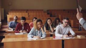 Группа в составе студенты слушает к учителю и пишет сидеть на таблицах в классе пока профессор говорит и акции видеоматериалы