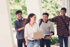 Группа в составе студенты университета идя снаружи совместно в кампус, Стоковое Изображение RF