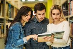 Группа в составе студент хочет найти некоторая полезная литература к подготавливать для экзамена университета 2 девушки и один вз стоковое фото rf