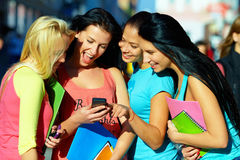 Группа в составе студенты беседует в социальной сети на телефоне Стоковая Фотография RF
