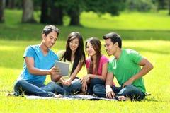 Группа в составе студенты изучая в парке стоковые фотографии rf