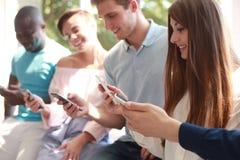 Группа в составе студенты наблюдая smartphones Молодые люди наркомании к тенденциям новой технологии Стоковое Изображение