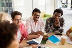 Группа в составе студенты средней школы сидя на таблице Стоковые Изображения RF