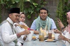 Группа в составе счастливое молодое мусульманское имеющ обедающий внешний стоковое изображение rf