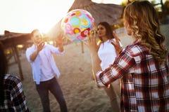 Группа в составе счастливое молодые люди играя с шариком на пляже Стоковое фото RF