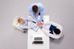 Группа в составе счастливые бизнесмены держа руки совместно пока сидящ вокруг стола Стоковые Фото
