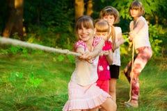 Группа в составе счастливые дети играя перетягивание каната снаружи на траве Веревочка детей вытягивая на парке Летнего лагеря стоковое фото rf