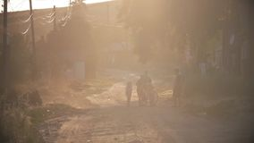 Группа в составе счастливые дети играя outdoors в деревне и ходе к камере, всех нося подобных одеждах knit на теплом акции видеоматериалы