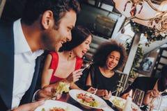 Группа в составе счастливые друзья встречая и имея обедающий стоковое фото rf