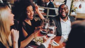 Группа в составе счастливые друзья встречая и имея обедающий стоковые фотографии rf