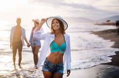 Группа в составе счастливые друзья имея потеху идя вниз с пляжа на заходе солнца стоковое фото rf