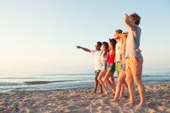 Группа в составе счастливые друзья имея потеху на пляже океана Стоковая Фотография