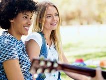 Группа в составе счастливые друзья при гитара имея потеху внешнюю Стоковое Изображение