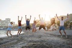 Группа в составе счастливые друзья скача на пляж Стоковое фото RF