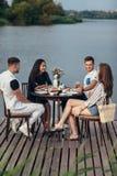 Группа в составе счастливые друзья собирая к иметь обедающий совместно стоковое фото rf