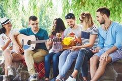 Группа в составе счастливые друзья с гитарой Пока одно из их играет гитару и другие дают ему взрыв аплодисментов стоковая фотография