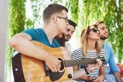 Группа в составе счастливые друзья с гитарой Пока одно из их играет гитару и другие дают ему взрыв аплодисментов стоковое фото