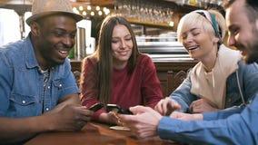 Группа в составе счастливые друзья хипстера наблюдая видео, фото по умному телефону совместно в баре, пабе акции видеоматериалы