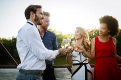 Группа в составе счастливые друзья partying и провозглашая тост напитки стоковые фото