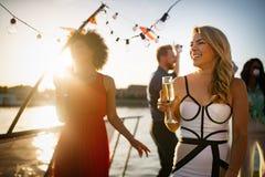 Группа в составе счастливые люди или друзья имея потеху на партии стоковые изображения