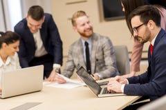 Группа в составе счастливые молодые бизнесмены в встрече на офисе стоковая фотография