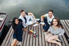 Группа в составе счастливые молодые друзья ослабляя на пристани реки деревянной стоковые изображения