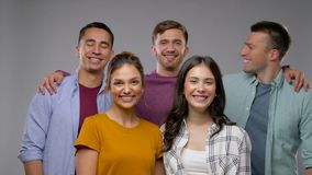Группа в составе счастливые усмехаясь друзья над серым цветом акции видеоматериалы