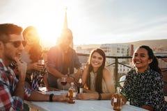 Группа в составе счастливое молодые люди имея партию стоковые фото
