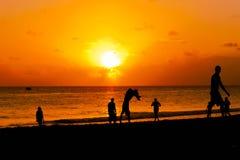 Группа в составе счастливое молодые люди скача заходом солнца пляжа Стоковые Фотографии RF