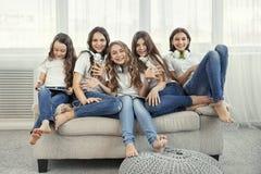 Группа в составе счастливые девочка-подростки с устройствами Социальные сети, приятельство, технология и концепция детей Стоковые Изображения