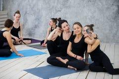 Группа в составе счастливые девушки в классе фитнеса на проломе смотря smartphone Стоковое фото RF