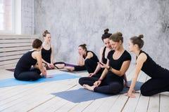 Группа в составе счастливые девушки в классе фитнеса на проломе смотря smartphone Стоковое Изображение RF