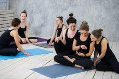Группа в составе счастливые девушки в классе фитнеса на проломе смотря smartphone Стоковые Изображения RF