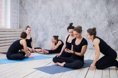 Группа в составе счастливые девушки в классе фитнеса на проломе смотря smartphone Стоковые Фотографии RF