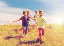 Группа в составе счастливые дети бежать outdoors Стоковые Изображения RF